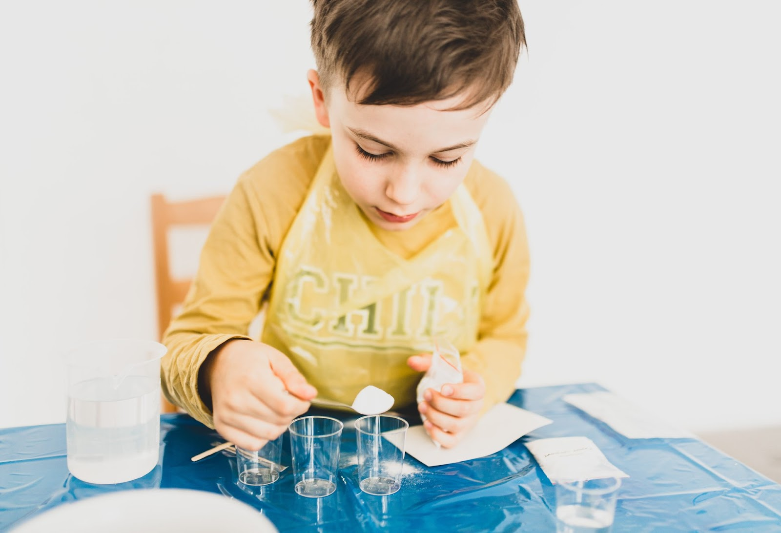 A young boy participates in an age-appropriate STEM activity with small cups and measuring spoons. He has covered himself with an apron and his table with a covering for safety purposes.