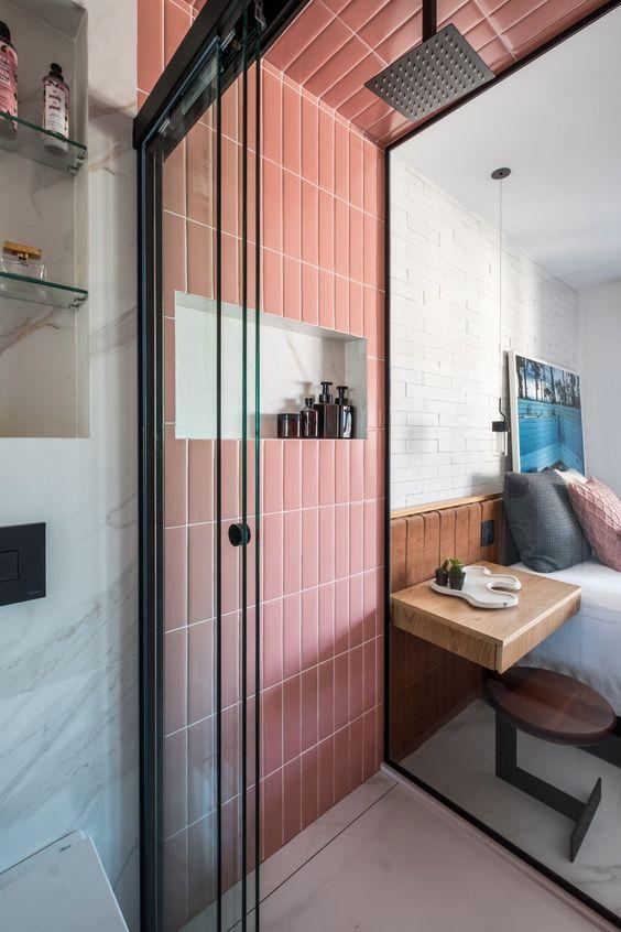 Banheiro com parede principal do box e teto com revestimento subway tiles rosa, box de vidro e piso branco