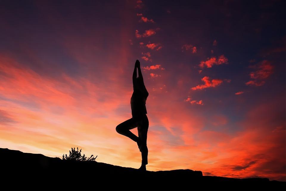 Persona haciendo yoga con atardecer de fondo