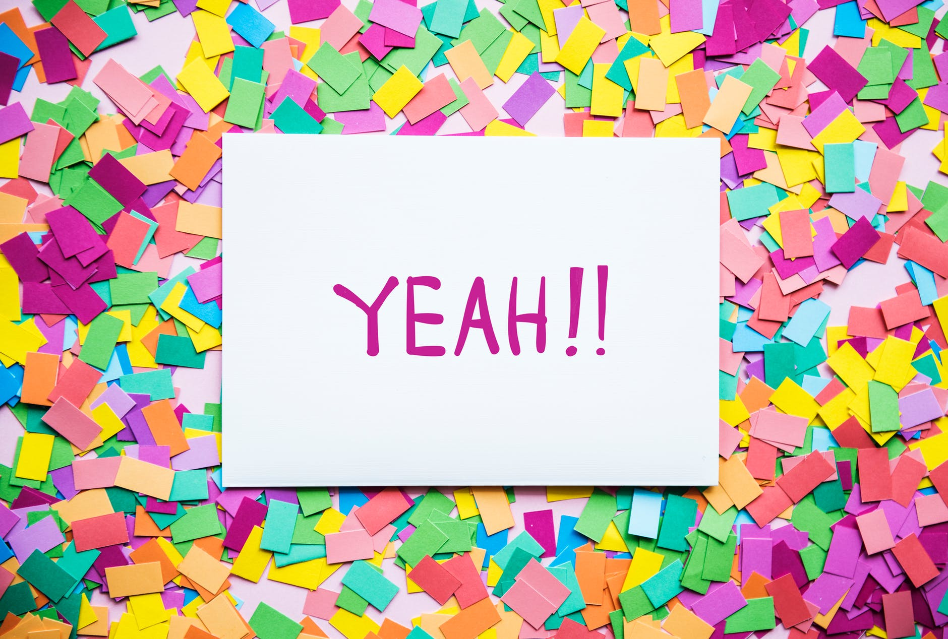 the word 'yeah!!' printed on a piece of paper, surrounded by colorful post-it notes.