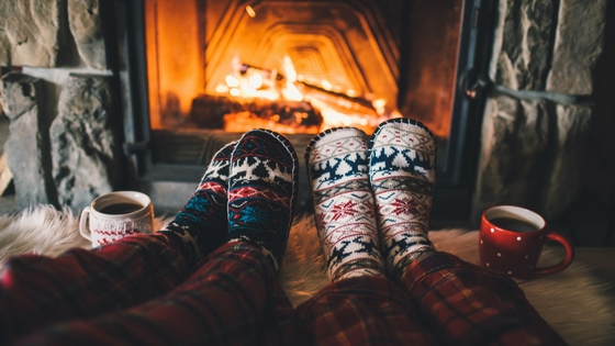 two people in slippers cozying up next to the fireplace