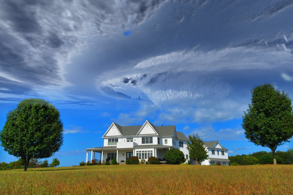 white and gray house between two green tall trees under gray clouds forming swirl during daytime