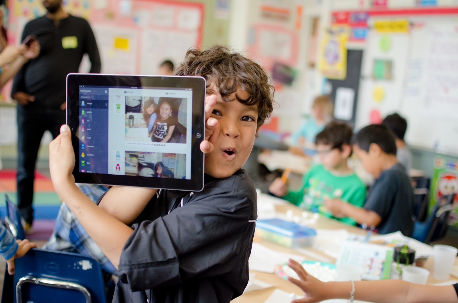 Online teaching platforms: A student holding up a tablet with ClassDojo displayed on the screen