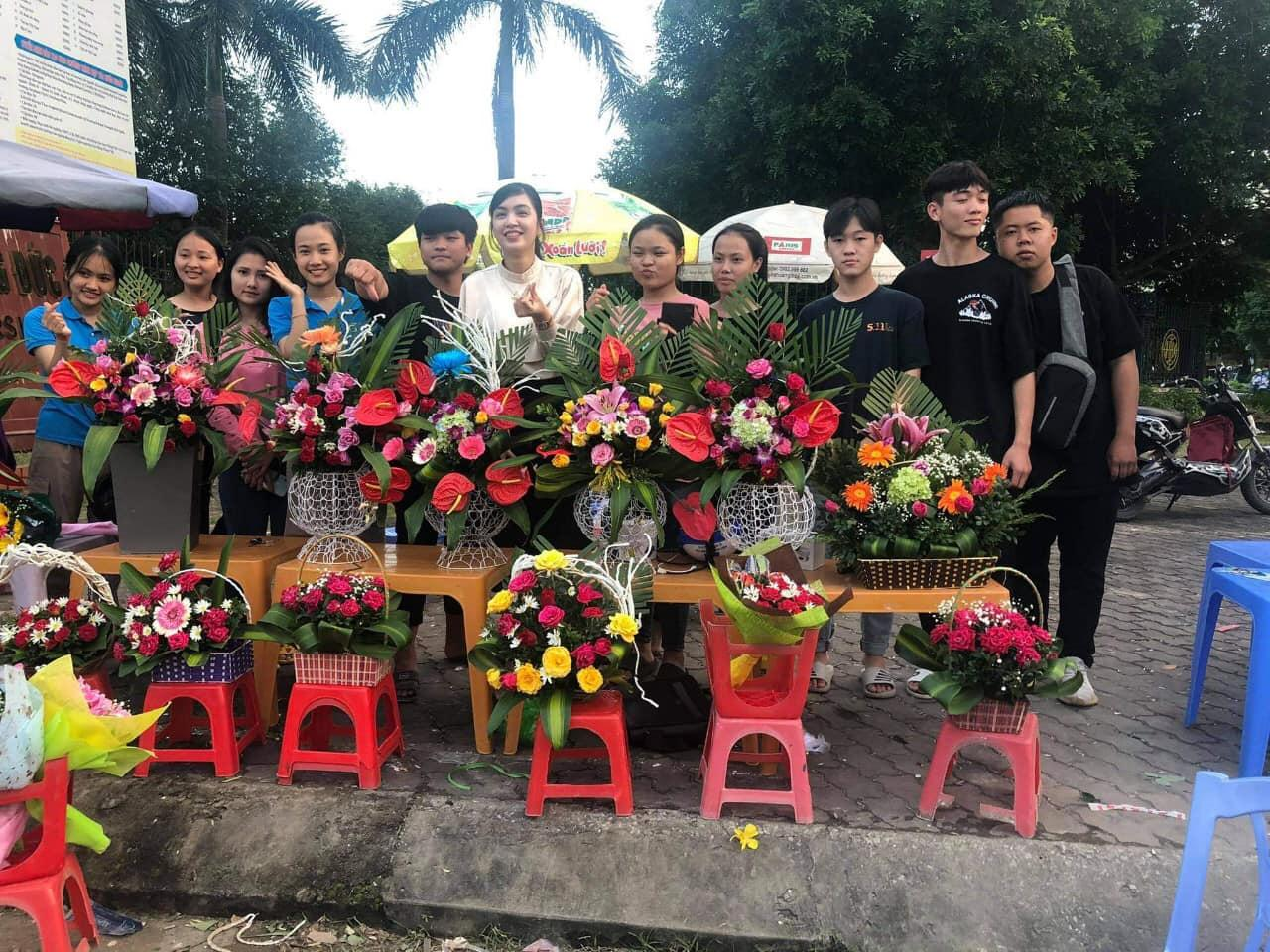 Image may contain: 11 people, people standing, flower and outdoor