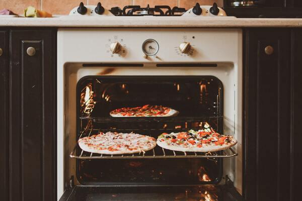 Foto de um forno aberto com 3 pizzas