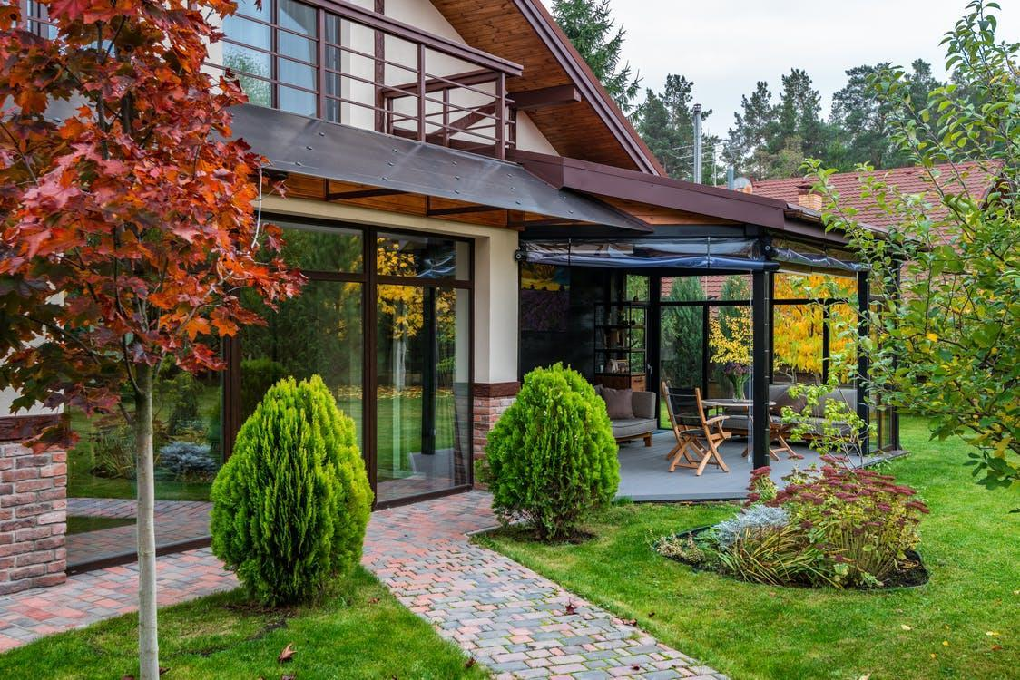 Exterior of contemporary house with cozy terrace and garden with bushes and trees on autumn day