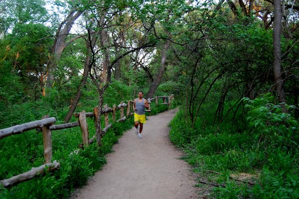 A man jogging through Barton Creek Greenbelt.
