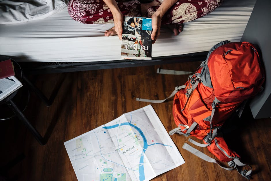 Person holding travel book with backpack and map; planning outdoor travel
