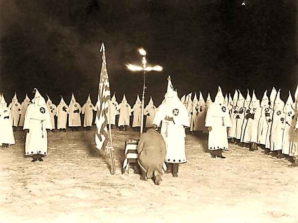Man kneels at a burning cross as a hooded Klan member stands over him with a chalice during a Ku Klux Klan nighttime initiation ceremony, 1920s....