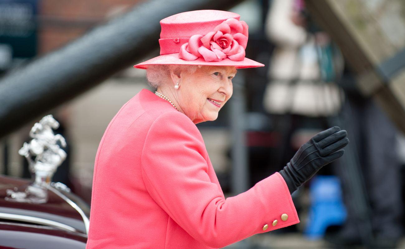 Queen Elizabeth II wearing full pink whilst smiling