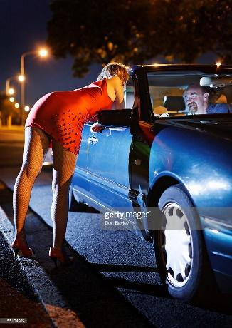 Eager would-be client chats up prostitute at car window : Stock Photo