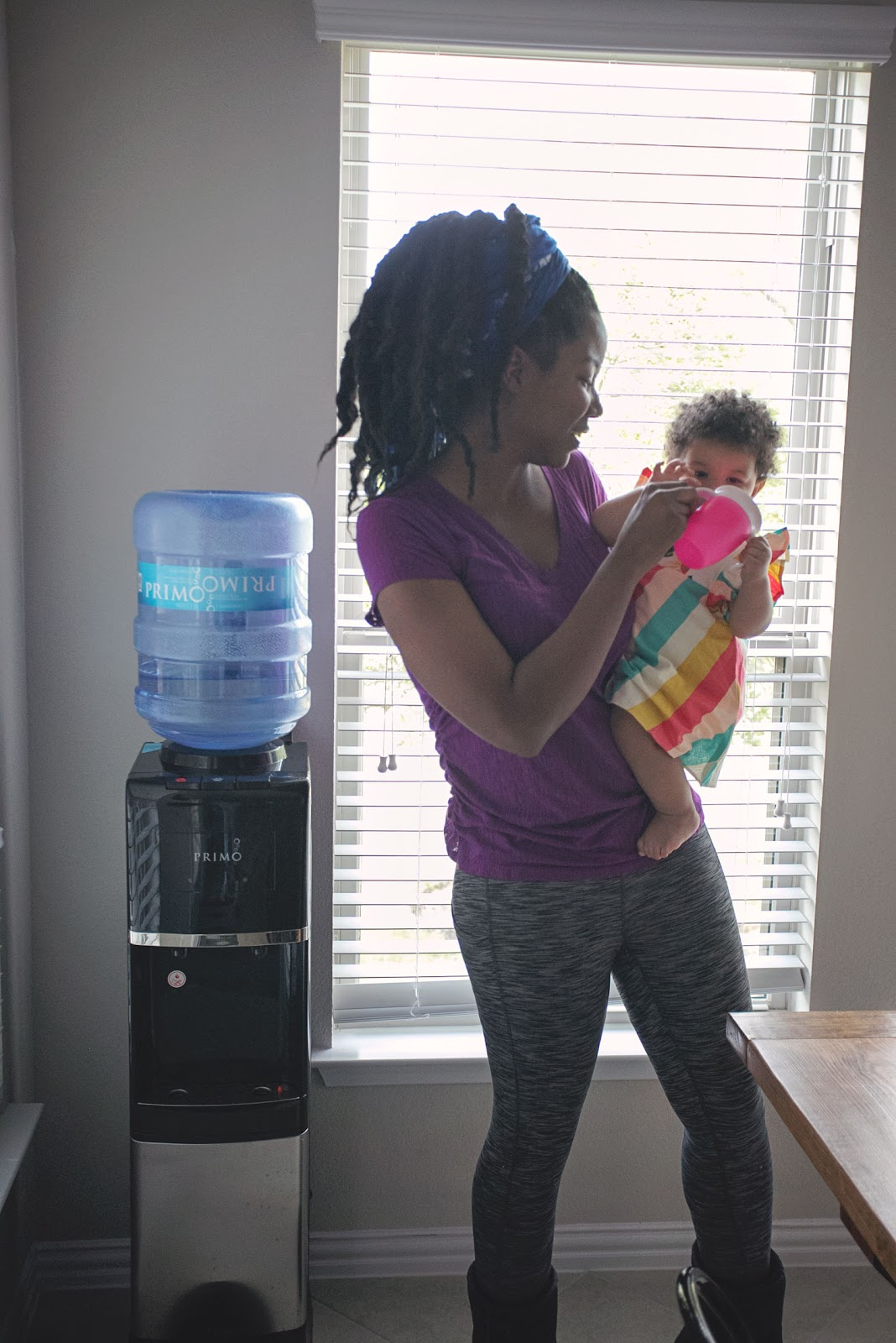 Black mom holding her biracial baby. Standing next to Primo water best water dispenser.