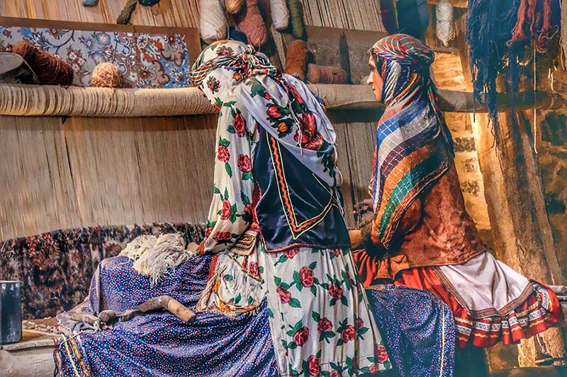 lots of colors in Persian carpets which is woven by two women dressed traditionally