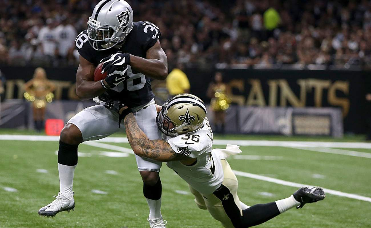 T.J. Carrie of the Oakland Raiders is tackled by Daniel Lasco of the New Orleans Saints during a game at the Mercedes-Benz Superdome in 2016, New Orleans, Louisiana.
