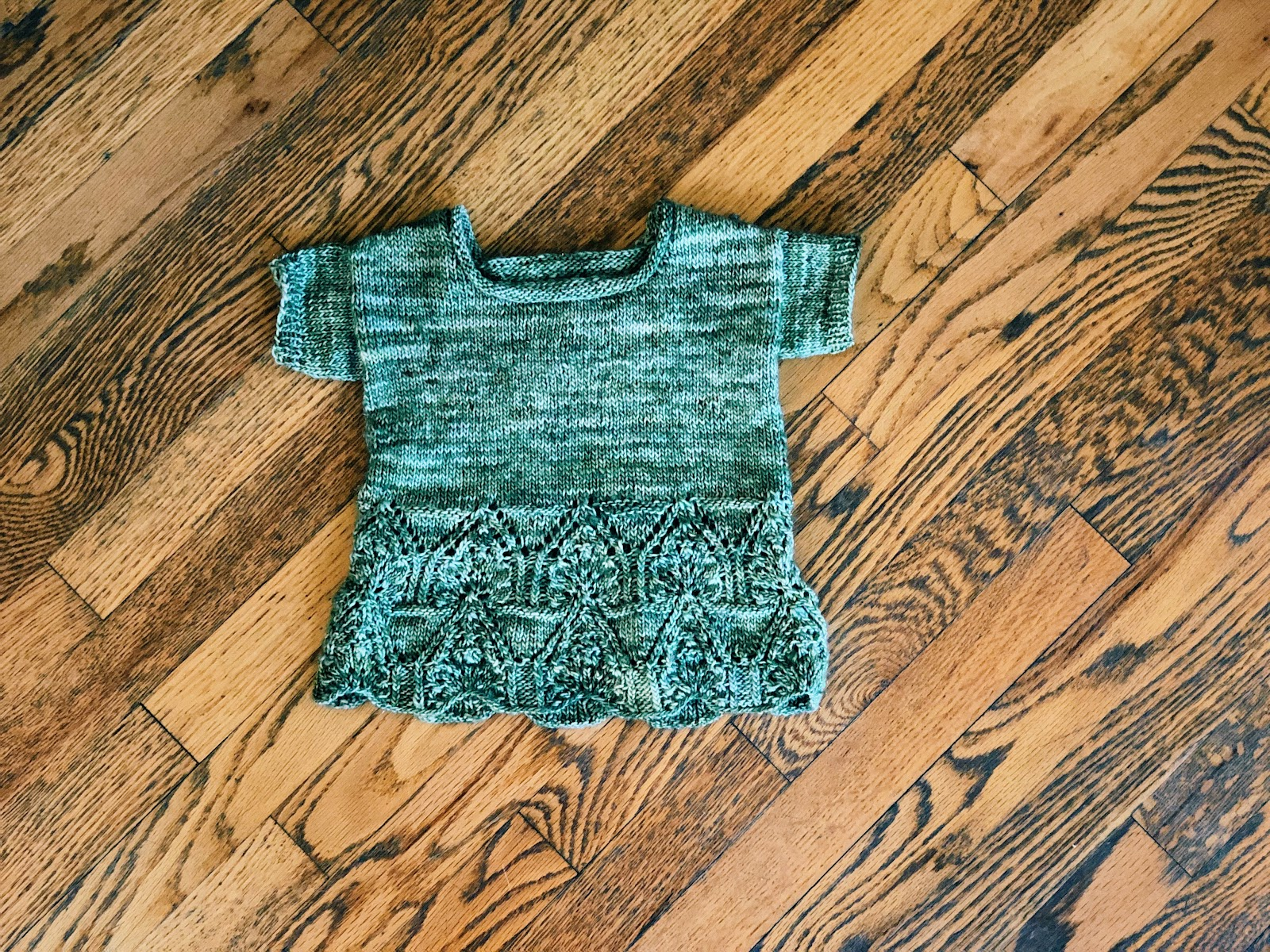 A small, blue, knitted shirt with a diamond knitted pattern along the bottom lays flat against a hard wood floor.