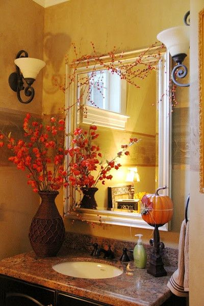 Bathroom sink decorated for fall with an orange pumpkin and a vase with orange flowers and red berries draped over the mirror.
