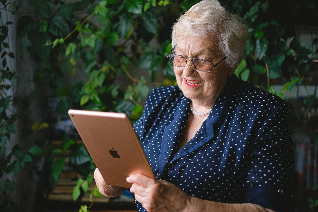 An old person holding a tablet Description automatically generated with medium confidence