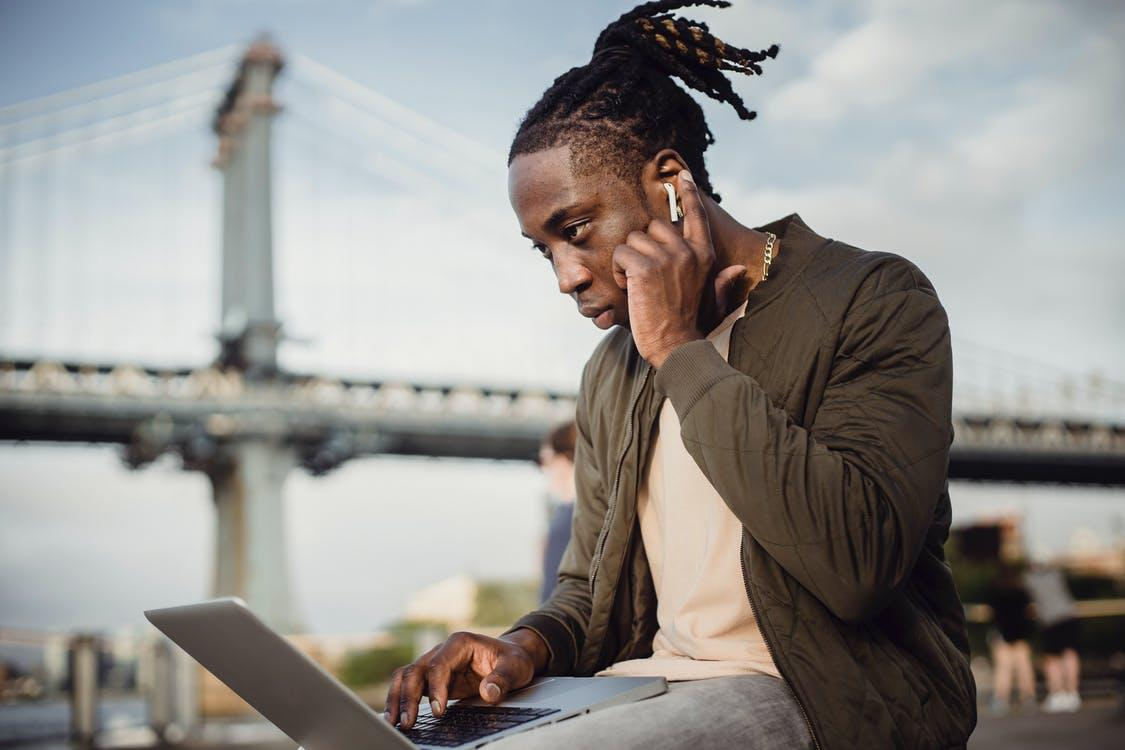 Low angle of concentrated black man in casual wear using laptop and earphones while working outdoors in park