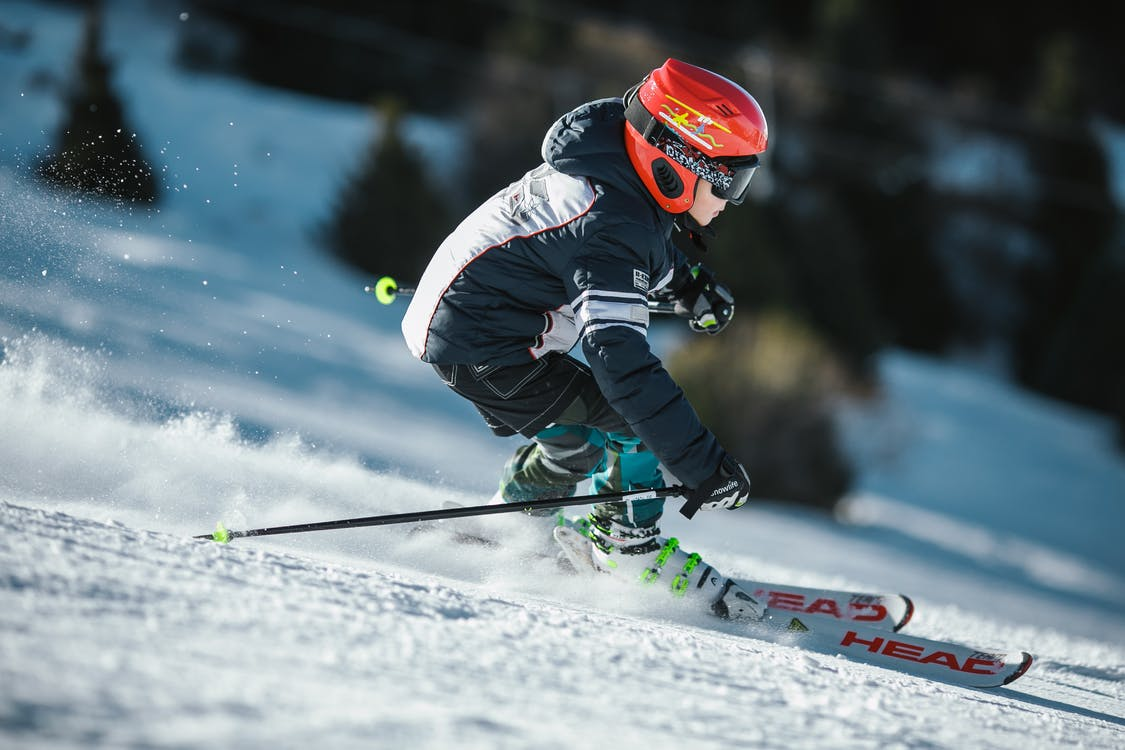 Man Doing Ice Skiing on Snow Field in Shallow Focus Photography