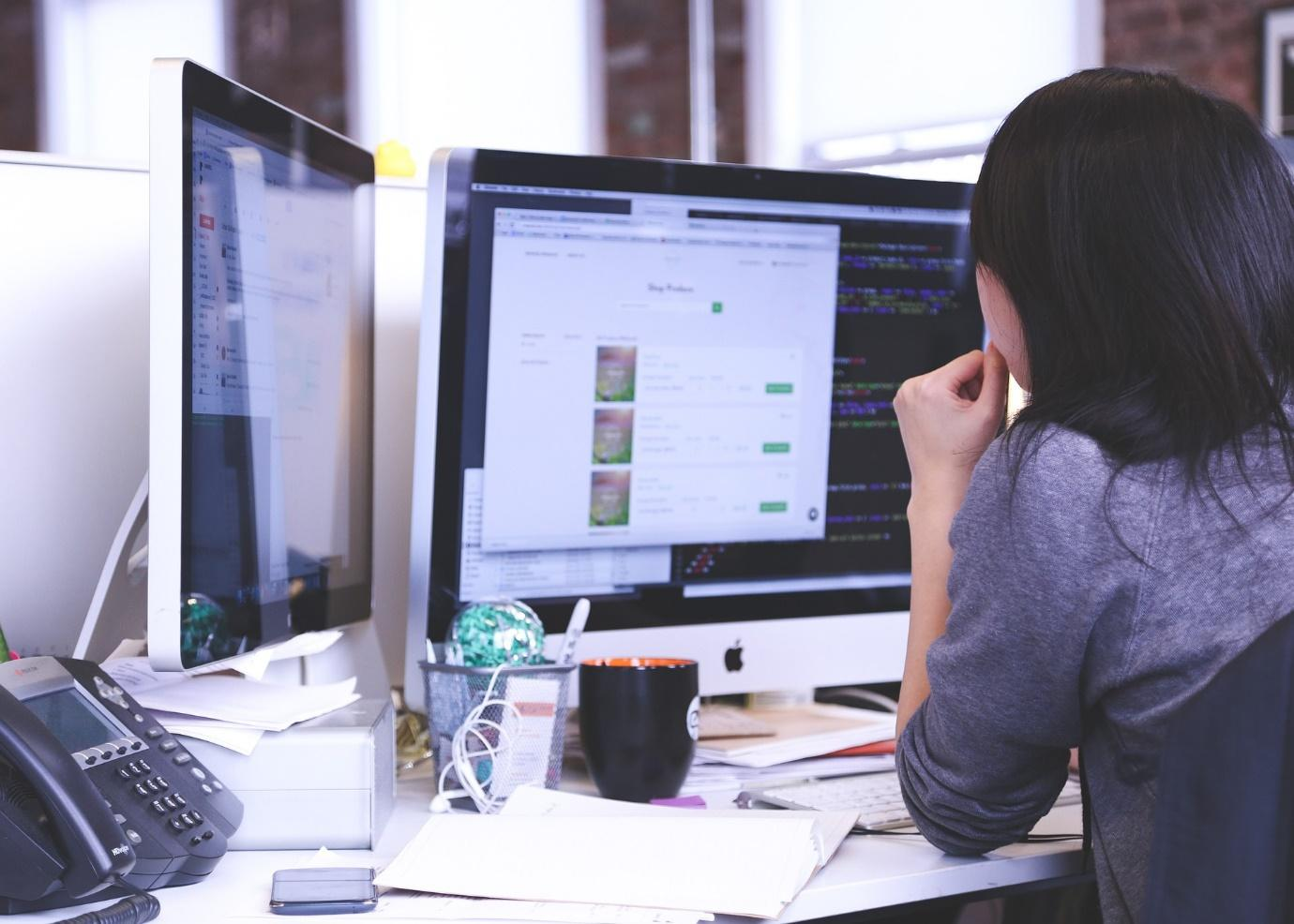 A person sitting at a desk looking at a computer screen  Description automatically generated with low confidence