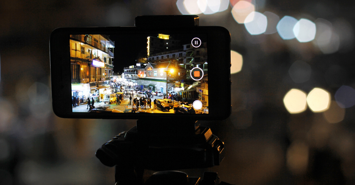 View through the screen of a cell phone shooting a video of night life in a city.