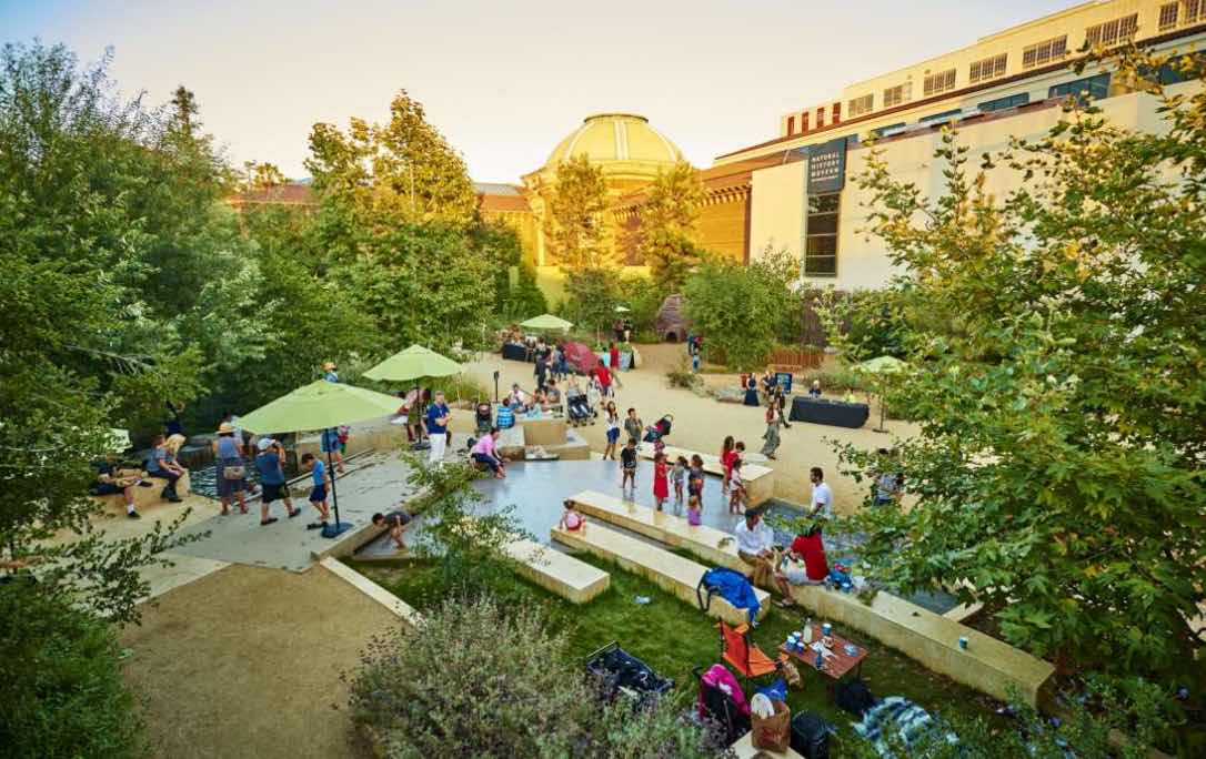 The Natural History Museum's backyard filled with people strolling at sunset