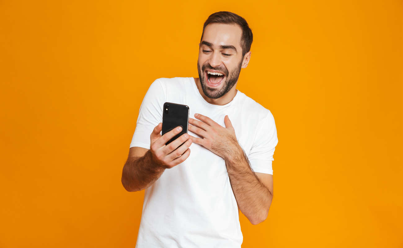man in casual wear smiling and holding smartphone