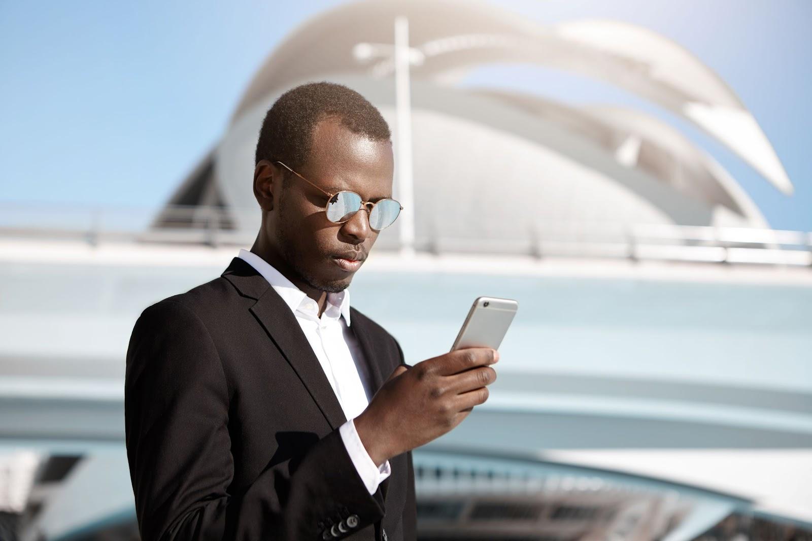 foto de um homem com roupas sociais e óculos escuros, mexendo em seu smartphone para realizar atividades de teletrabalho na modalidade remote everything