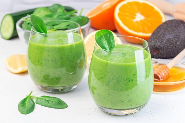 Зеленый детокс смузи с авокадо, шпинатом, огурцом, апельсином, лимоном и медом Premium Фотографии