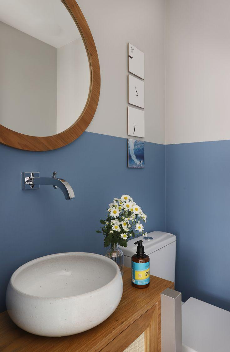 Banheiro com técnica de pintura meia parede azul e branca, gabinete amadeirado, cuba branca e espelho redondo.