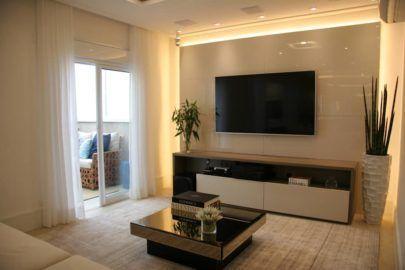 Sala de estar com cores neutras, hack bege, mesa de centro de espelho e plantas.