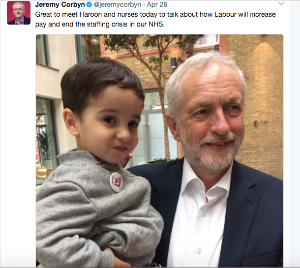 "Screenshot of Jeremy Corbyn UK Labour Party Leader holding young male child with the tweet ""Great to meet Haroon and nurses today to talk about how Labour will increase pay and end the staffing crisis in our NHS"""