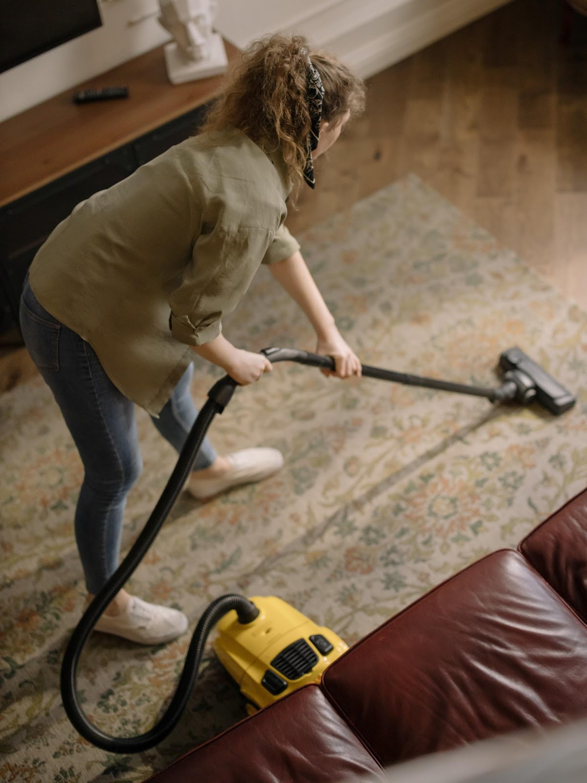 lady spring cleaning her home - vacuuming the carpet
