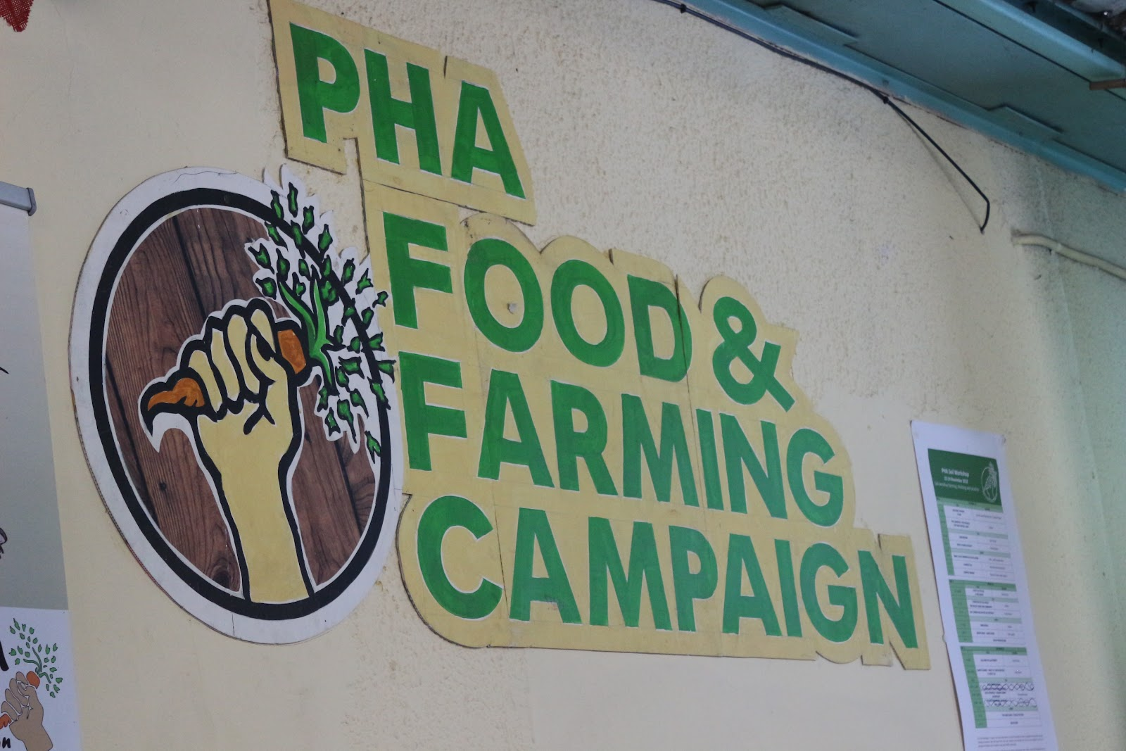 Sign that says PHA FOOD & FARMING CAMPAIGN on a yellow wall. To the left of the sign is a hand holding a carrot behind a background painted like hardwood circle.