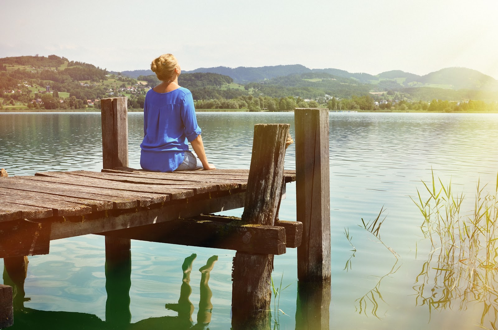 A woman sitting on a dock, enjoying the sun and nature