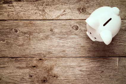 Piggy bank on the old wooden background, top view