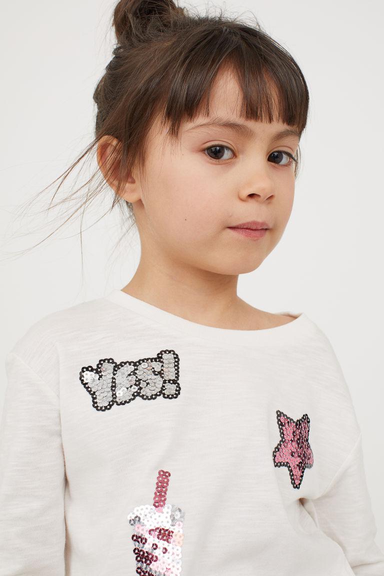 Dżersejowy top z cekinami - Naturalna biel/Gwiazdy - Dziecko | H&M PL 1