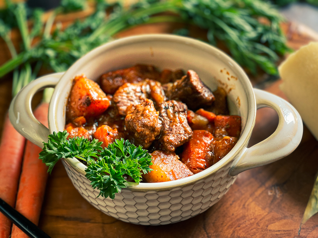 Beef stew in a bowl surrounded by vegetables