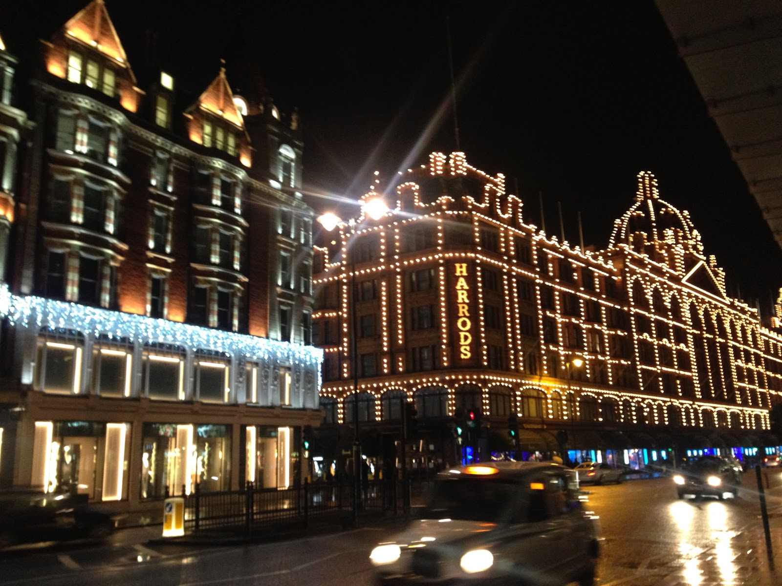 harrods luxury department store in london. Decorative lighting on the building's exterior facade seen during night time, london taxi passing the street in foreground.