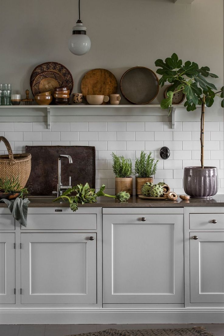 rustic scandinavian kitchen with open shelving, white shaker cabinets, white subway tile backsplash, minimalist hardware, potted plants and decorative dishware