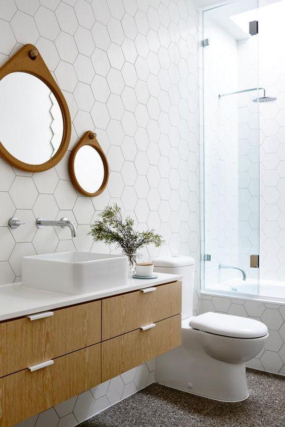 Banheiro com revestimento hexagonal branco por todas paredes, piso imitando pedras, armário amadeirado com bancada e cuba branca, espelhos redondos com moldura amadeirada e box de vidro