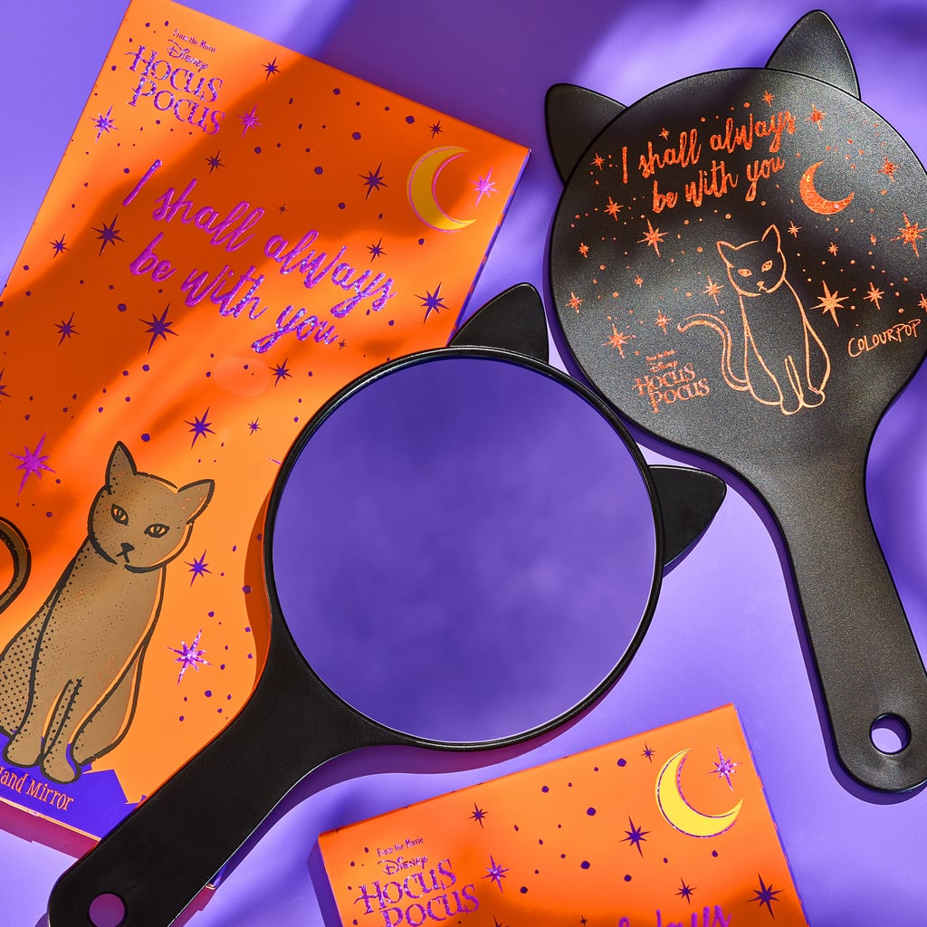 """Orange box with purple foiled design that says, """"I will always be with you."""" A black cat is sitting below the writing. A black cat-shaped handheld mirror lays on top."""