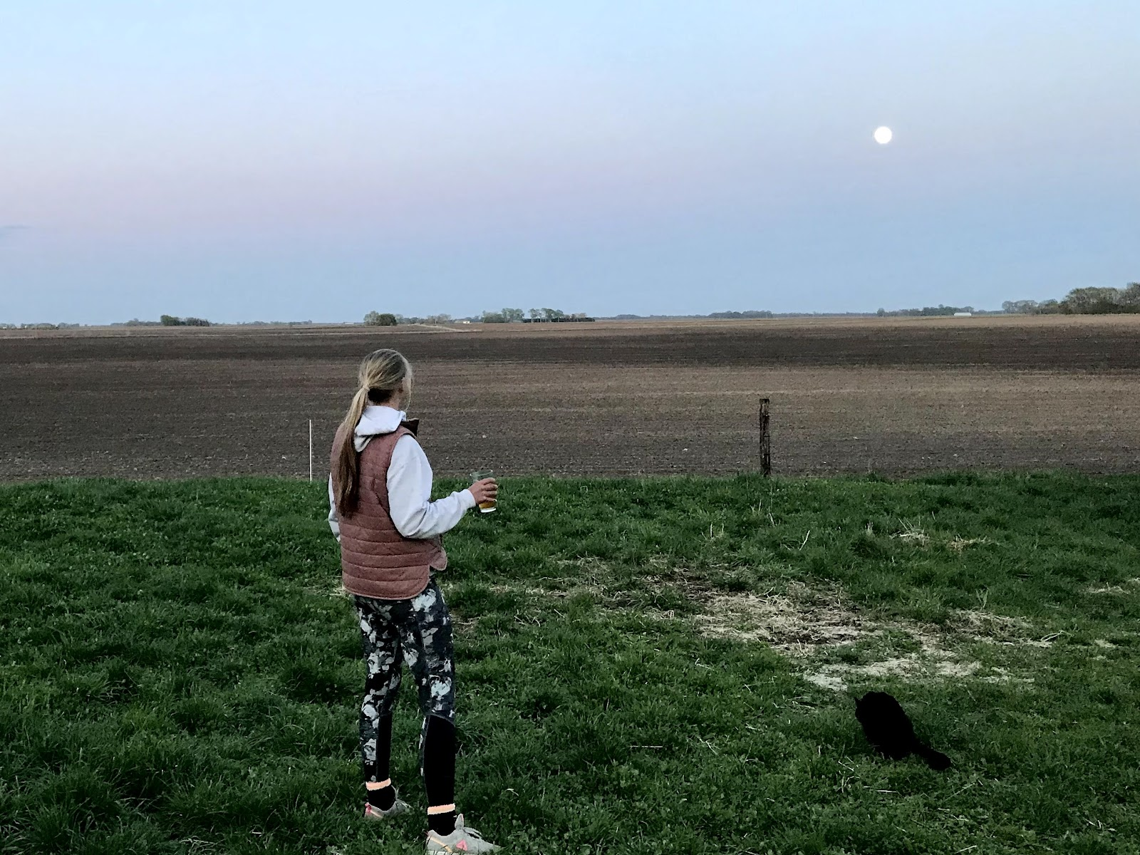 Annie stands looking at the distant moon with cat sitting nearby.