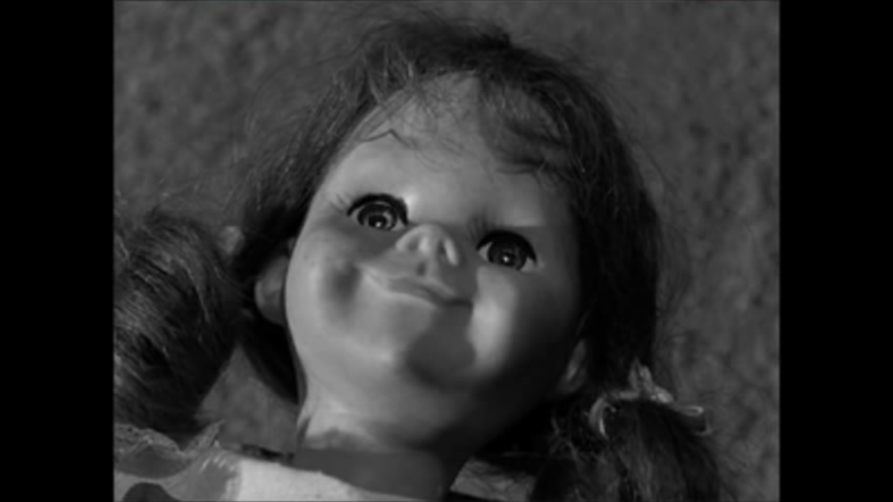 A black and white screen cap from The Twilight Zone. Close up on a doll's face (Talky Tina) looking straight up with an unsettling grin.