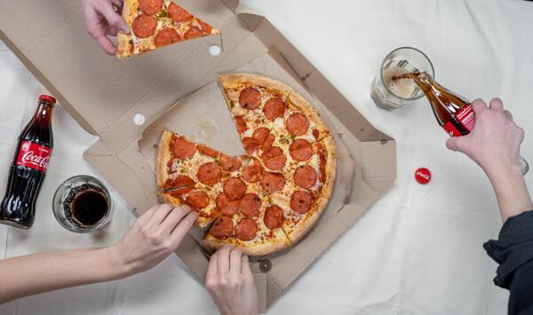 Foto tirada de cima de uma pizza e mãos pegando alguns pedaços