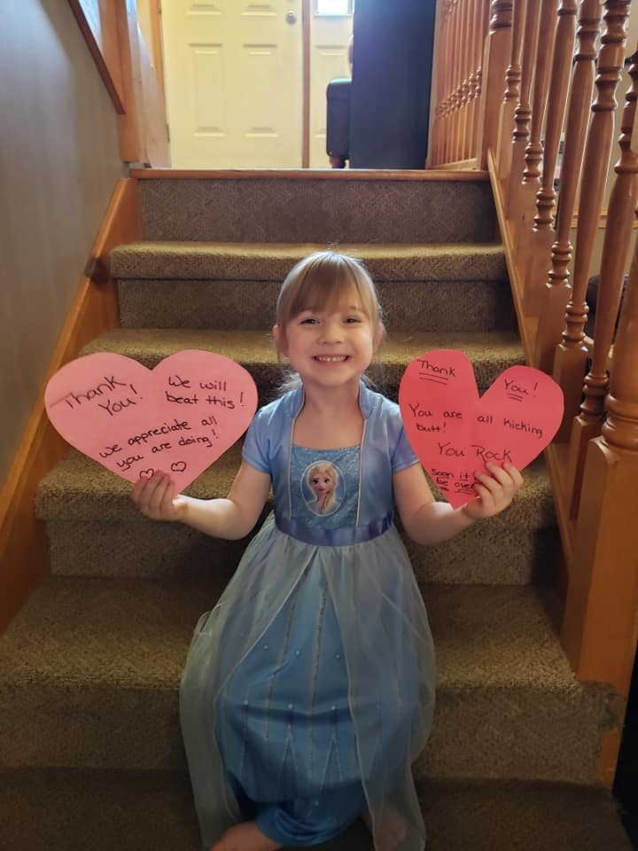 Little girl holding paper hearts