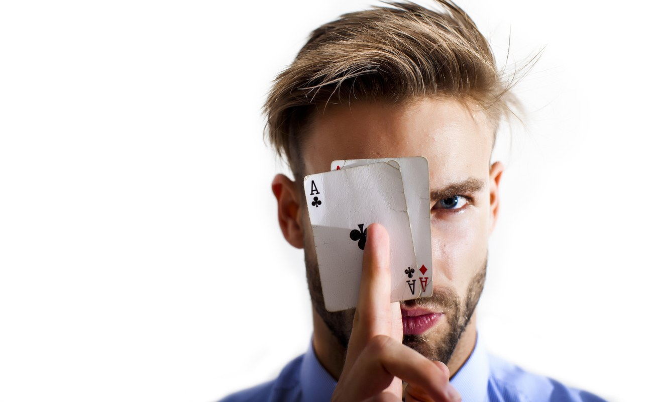 Young man with two ace cards held up to face
