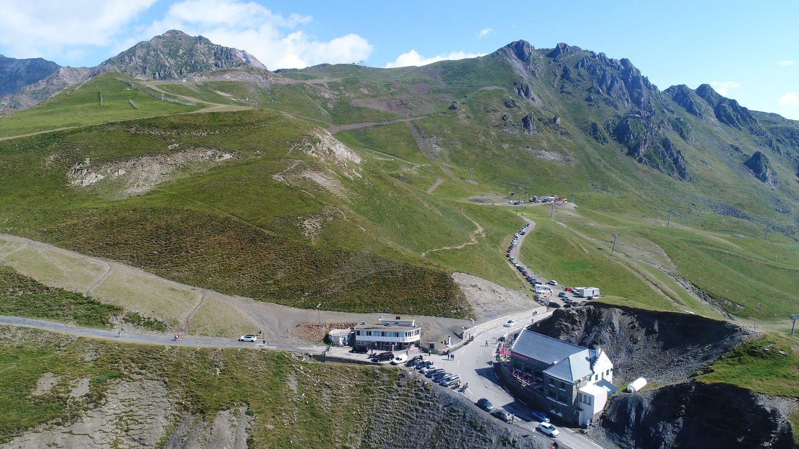 Climbing Col du Tourmalet by bike - drone aerial photo of col - cyclists, restaurant, statue, Le Géant, col sign