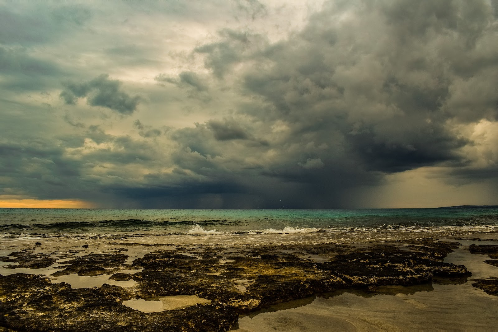 This is an image of dark rain clouds far in the distance over the ocean, as well as a beach covered in seaweed and tidepools. The ocean and weather are both studied through different branches of geoscience.