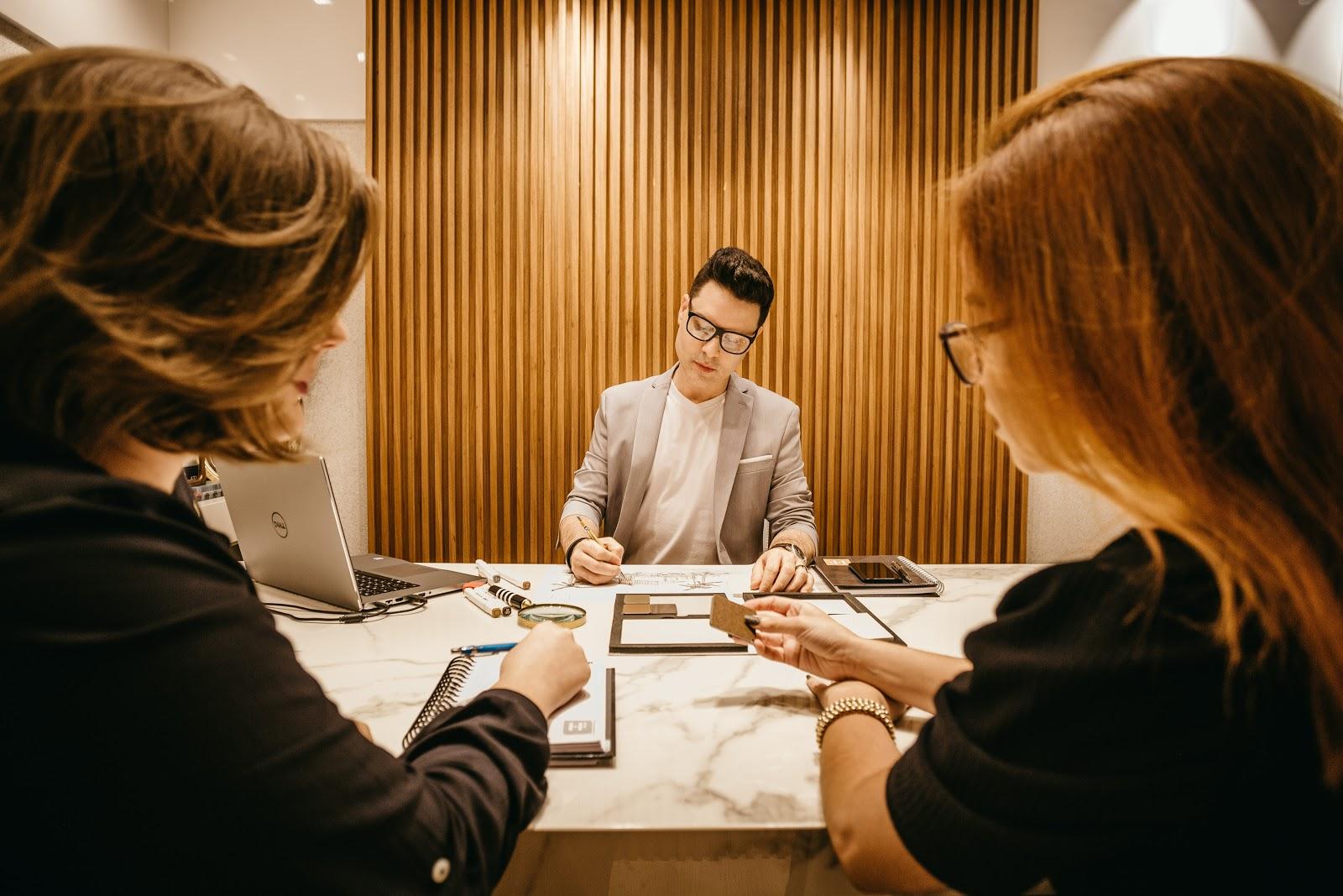 Um homem escrevendo anotações com duas mulheres em uma entrevista de emprego.